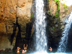 Visitors swimming in a lagoon under a waterfall