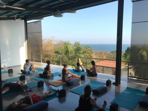 A group of people performing yoga on a rooftop deck overlooking beautiful scenery